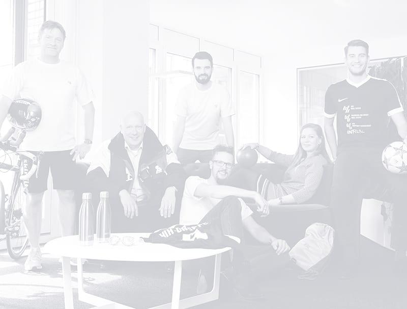 Schwarz-Weiß-Bild, das sechs Menschen mit Sportgegenständen zeigt, die auf und neben einer Couch sitzen und stehen