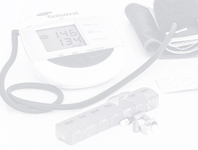 Schwarz-Weiß-Bild von einem Blutdruckmessgerät und Tabletten