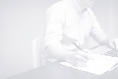 Schwarz-Weiß-Bild von einem sitzenden Mitarbeiter, der Notizen aufschreibt